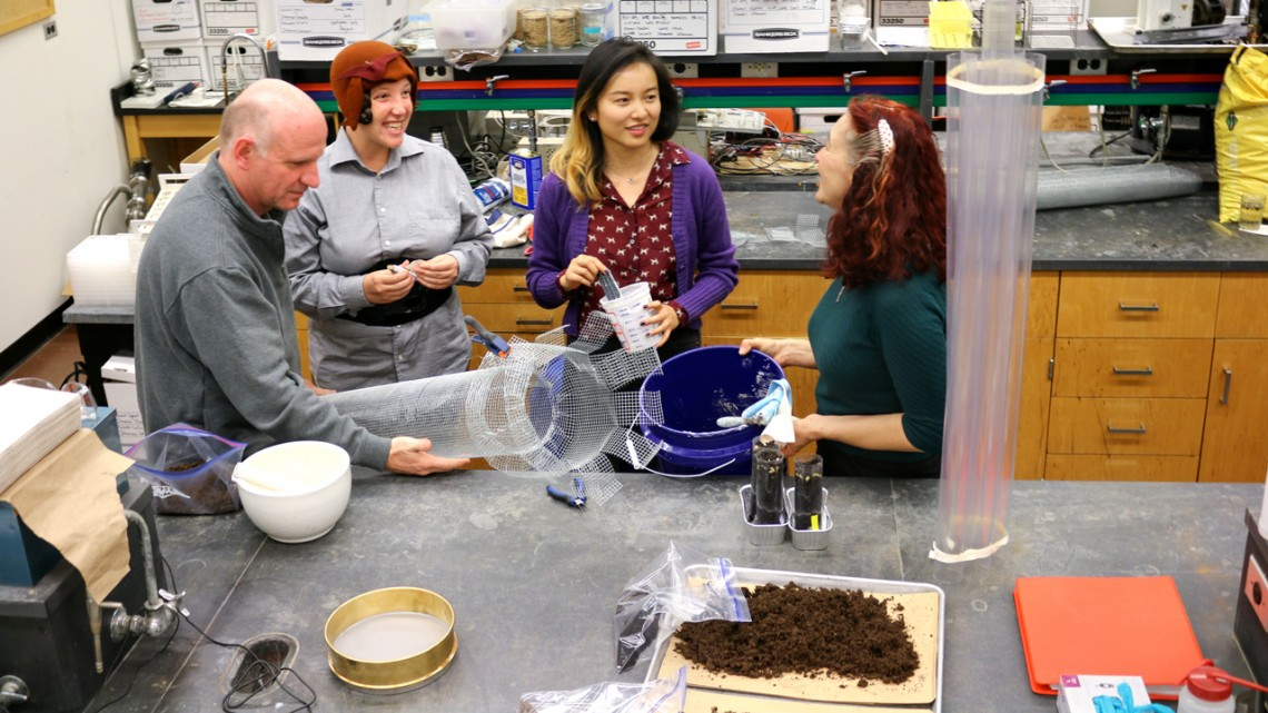 People gather around a soil art project in a lab
