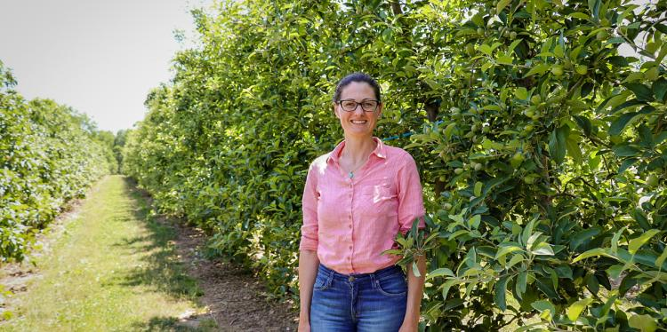 Poliana Francescatto stands in a orchard