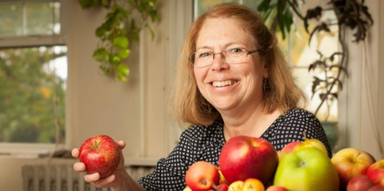 A smiling woman holds an apple next to more apples piled on a table