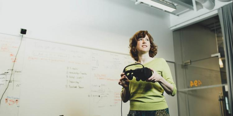 A woman standing in a classroom looking off to the side while holding a pair of virtual reality goggles