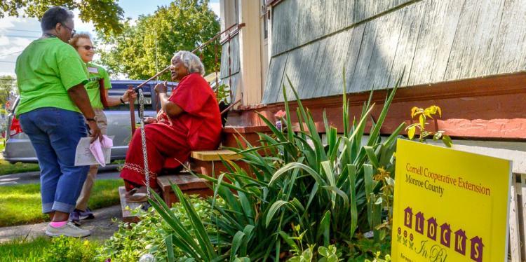 A black older woman sitting on her front stairs in front of her garden