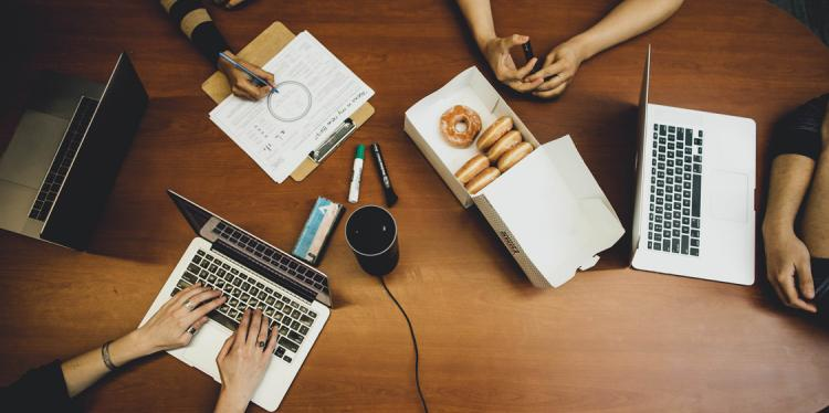 An arial view of men and women sitting at a table with laptops, paper and donuts, collaborating