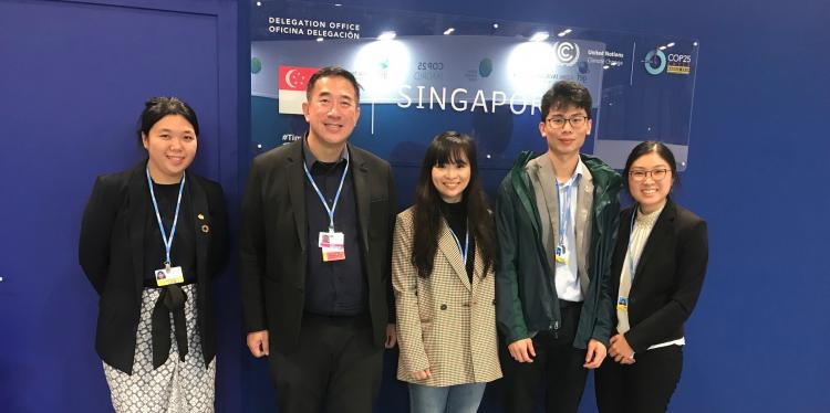 Four college students and one man stand in front of a sign for the delegation of Singapore