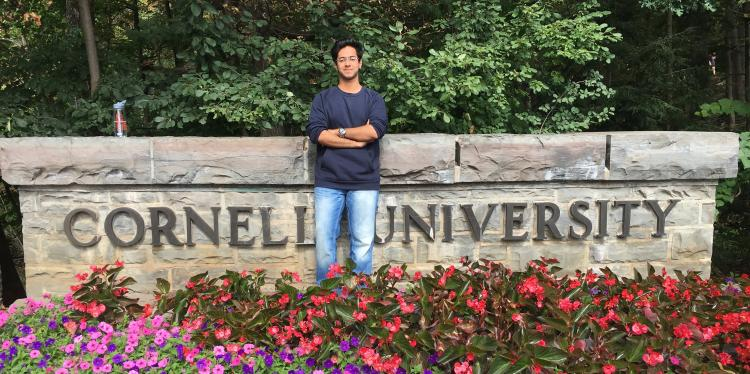 a college-aged man stands in a flower garden by a sign that reads Cornell University