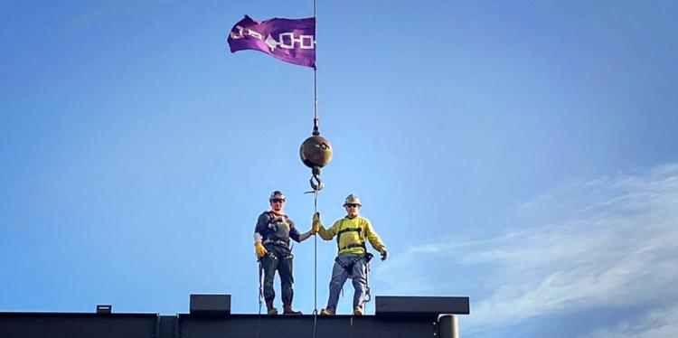 Two men stand on a construction scaffold flying a purple flag