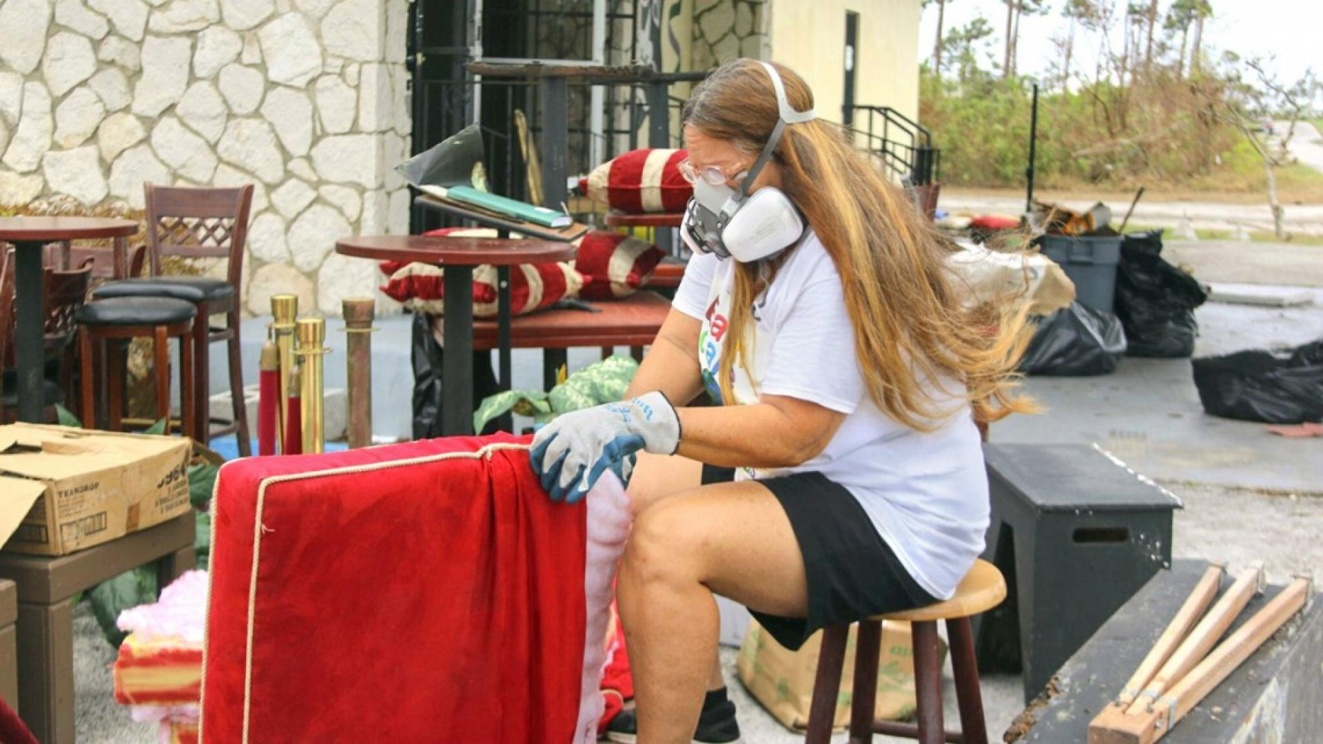 A woman wearing a mask cleaning a couch cushion outside.