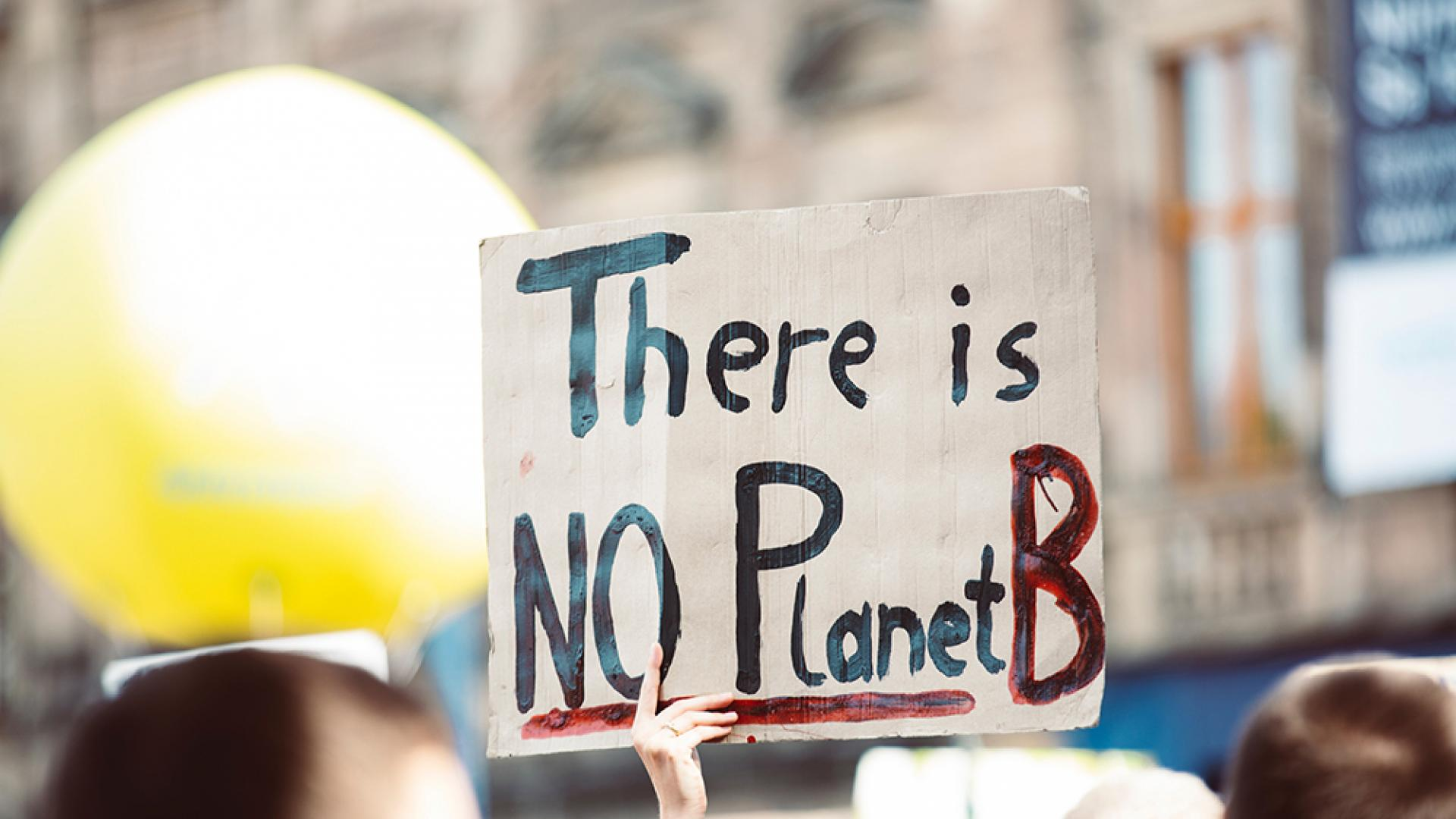A protester holding a sign that says there is no planet B
