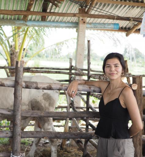A female student standing in front of a large penned farm animal