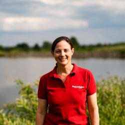 A woman in a red shirt stands in front of a pond and greenery