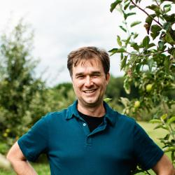 A man stands smiling in a fruit orchard