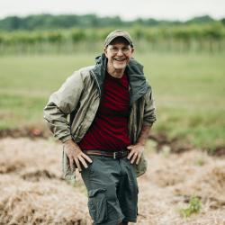 Man in field smiles.
