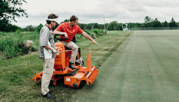 researchers examining turf grass