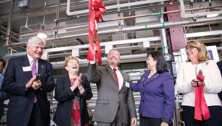 A group of men and women standing in a large space conducting a ribbon cutting and clapping