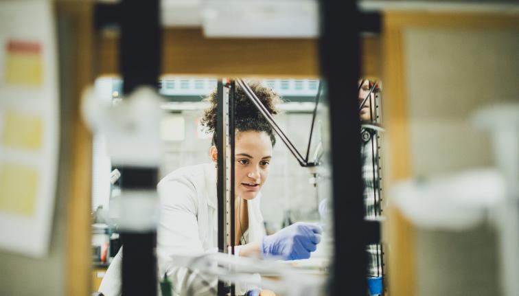 woman in lab coat works in laminar flow hood