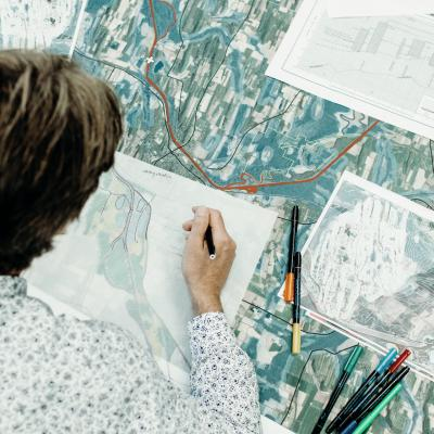 A person sketching a document related to landscape architecture.