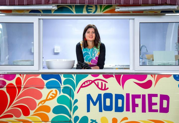 A woman standing and looking out a window of a colorful food truck