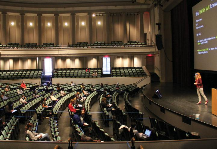 A female faculty member standing on a stage in a large performance hall to students scattered in the chairs below