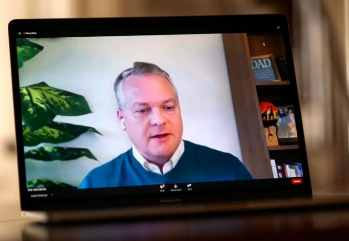 Chris Barrett speaking during a webinar on a labtop