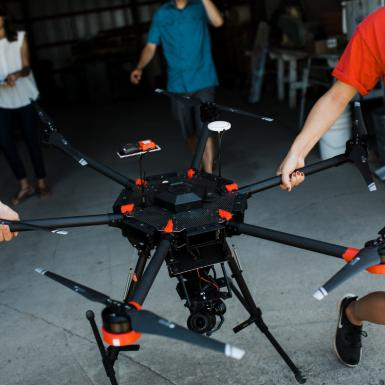 Students carrying a drone