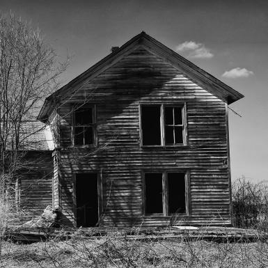 A black and white photo of an abandoned house with a leaf-less tree in front of it