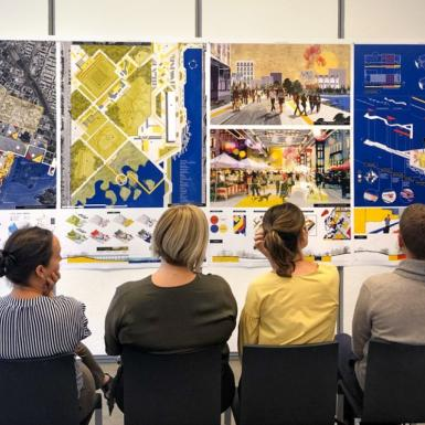 Several men and women sitting with their back to the camera looking at colorful posters of landscape architecture with a young woman in the front of the room presenting the posters