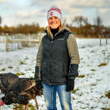 A woman standing outside in a snow-covered field with turkeys behind her