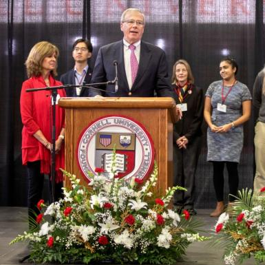 Men and women standing on a stage behind a man standing and speaking at a podium