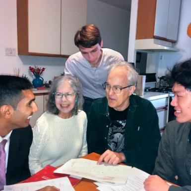 Three young men talk with an older couple around their kitchen table.
