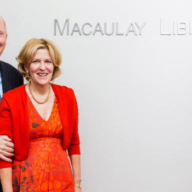 A man and woman standing in front of a white wall with a sign that says Macaulay Library