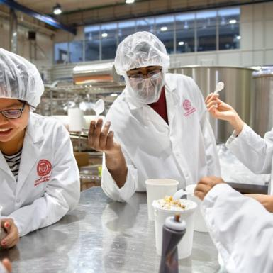 Male and female students in white lab jackets and hair nets standing around a metal table testing ice cream