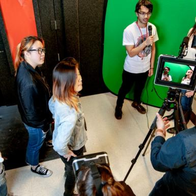 Male and female students working in a multimedia studio with a camera