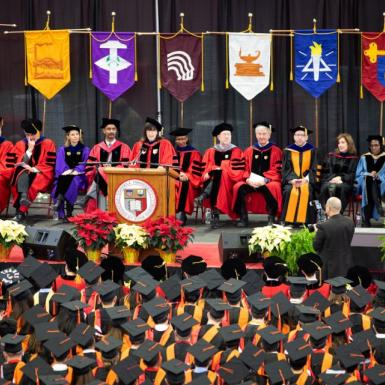 A graduation ceremony with the faculty sitting on stage in red robes