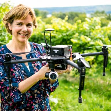 Woman stands with drone in middle of vineyard