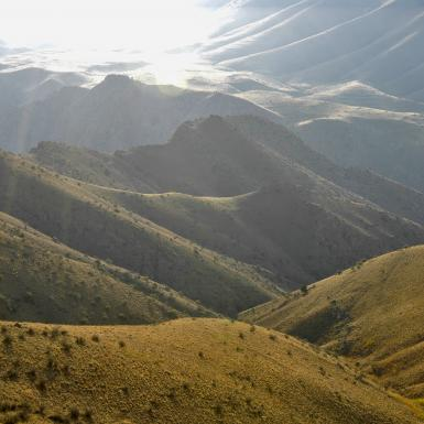 The sun shines down upon rolling mountains on the Armenian countryside