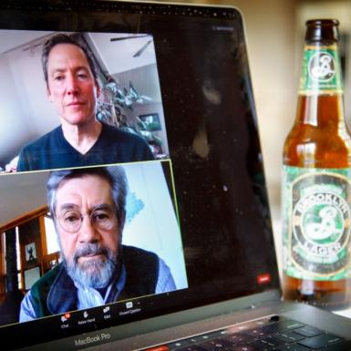 A computer laptop screen shows two men discussing beer.