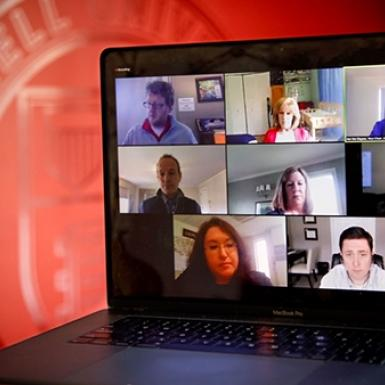 A laptop screens shows 7 people on a Zoom call.