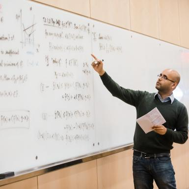 a bald man with glasses writes a complex equation on a whiteboard