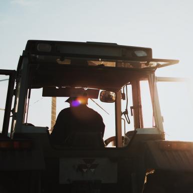 a person sitting in a tractor in a field with the sun setting behind him