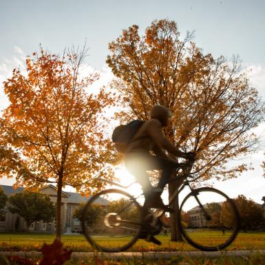 A student riding a bike in a college quad