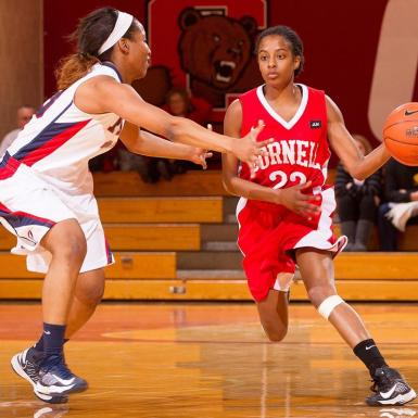 A female basketball player tries to dribble around an opponent
