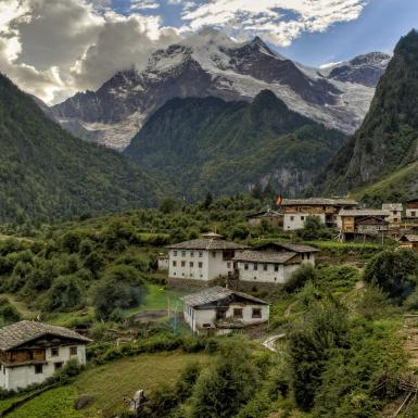 Village in a valley in Nepal with mountains in the background