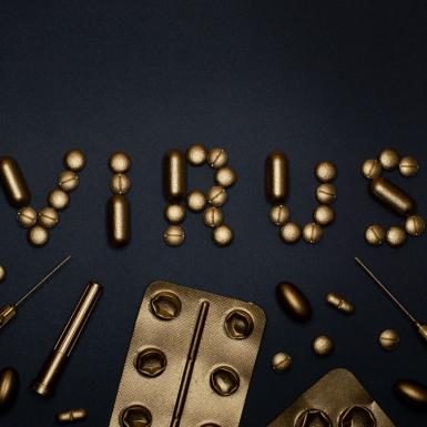 """Virus"" spelled out in gold pills with gold medical equipment"