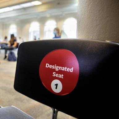 "a desk that has a red sticker on it reading ""designated seat 1"""