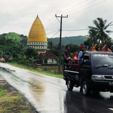 Group rides in the bed of a pick up truck in rural Indonesia