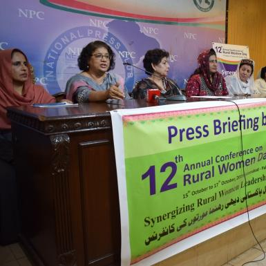 6 women sit at press conference table