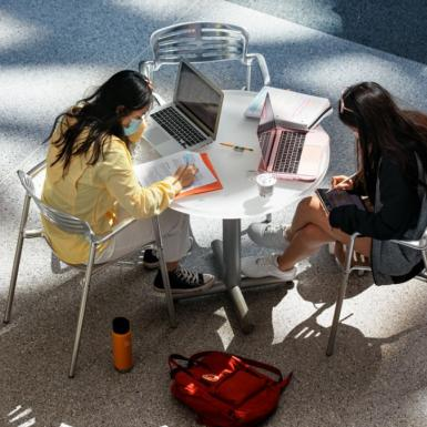 Two students sitting indoors and working at a table