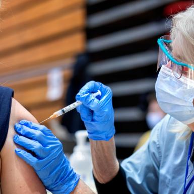 A person giving another person a vaccination indoors