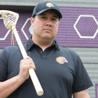 Picture of man holding a lacrosse stick in front of the side of a grey and purple building.