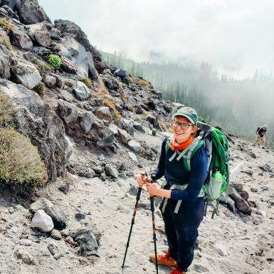 Ginny Moore hiking outside up a mountain carrying hiking poles and wearing a hate and backpack
