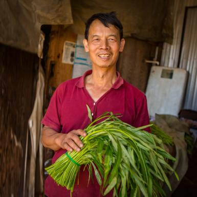 A Chinese farmer holds produce.
